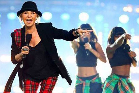 Lulu wearing black hat, tartan trousers and black suit jacket singing with two female backing singers