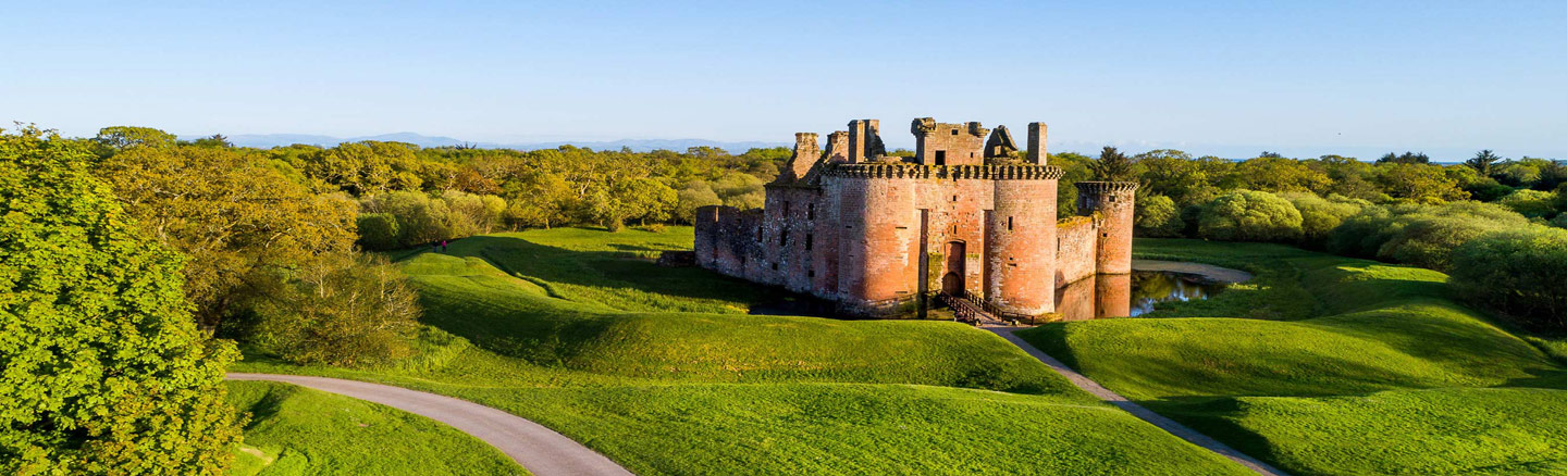 Encircled by a moat Caerlaverock Castle sits in a clearing surrounded by trees