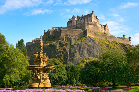 Edinburgh Castle atop rock viewed from Princes Street gardens with fountain in foreground