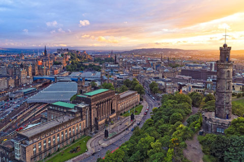 looking down on to Edinburgh cityscape with sun setting in background