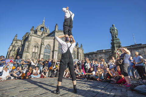 male street performer with man on his shoulders surrounded by audience during Edinburgh Fringe