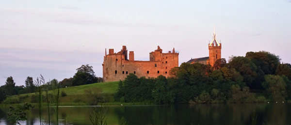 ruins of Linlithgow Palace at sunset next to Linlithgow Loch and partly obscured by trees