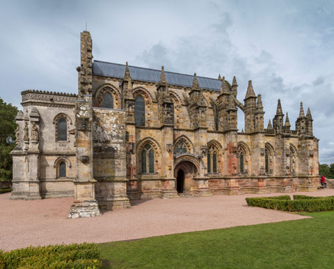 Rosslyn Chapel-  stone chapel with turrets and arched windows with gardens in foreground