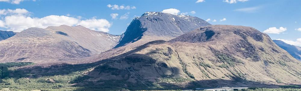 Panoramic view of Ben Nevis in bright sunshine and blue sky with scattered white clouds