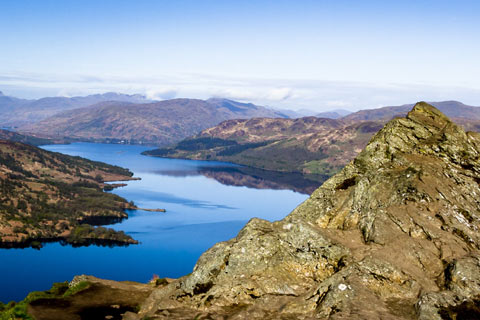 Loch Katrine with mountains on either side on bright day with clear blue sky