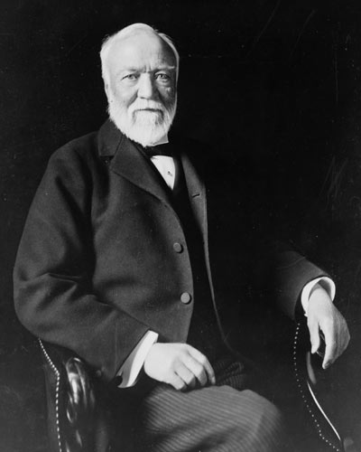 Black and white photogrph of Andrew Carnegie, seated with partly bald head and white beard