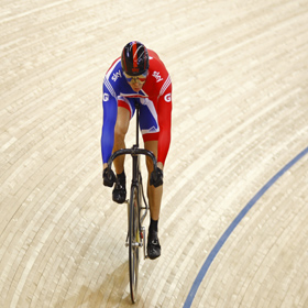 Sir Chris Hoy - cycling in red, white and blue colours in indoor arena