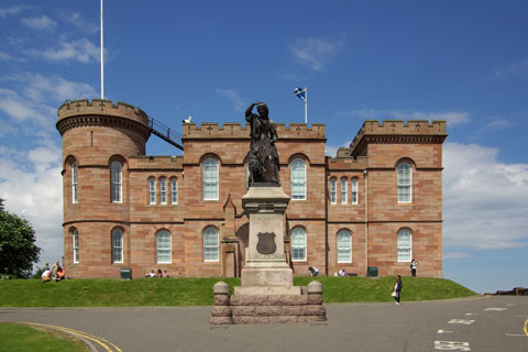 Flora MacDonald Statue - statue of young woman with arm raised, in front of Inverness Castle