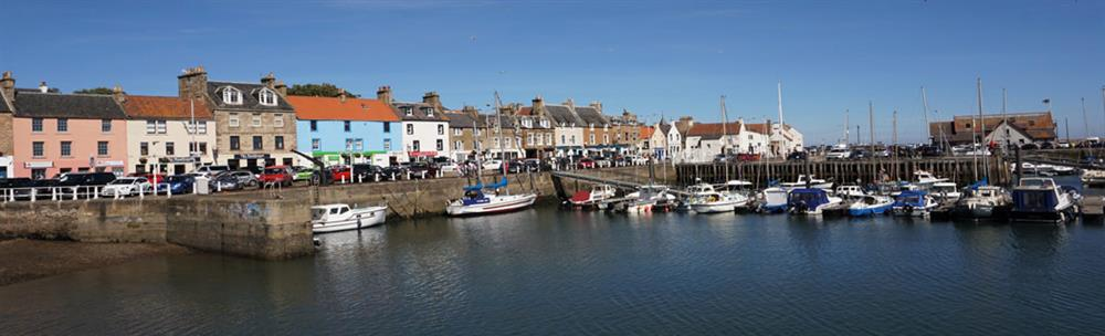 colourful houses and boats in the blue water at Anstruther harbour on a bright day