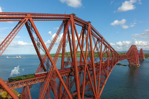 steam train on the Red iron Forth Rail Bridge crossing the River Forth on a bright day