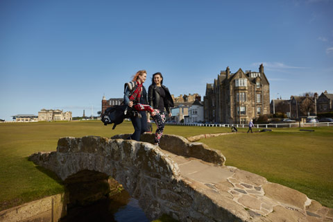 Two young women carrying golf clubs walking over the small Swilcan bridge at St Andrews golf course