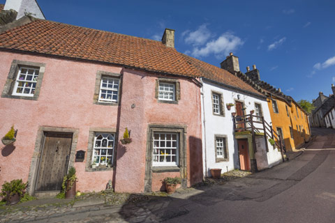 street winding uphill with pink, white and yellow cottages on a bright day