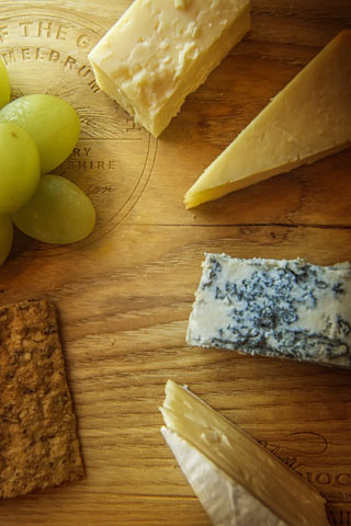 a selection of 4 cheeses with oatcake and grapes