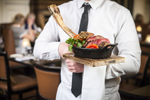 Waiter in white shirt and black tie carrying basket with steak
