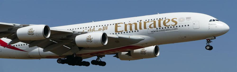 Emirates plane in flight with blue sky