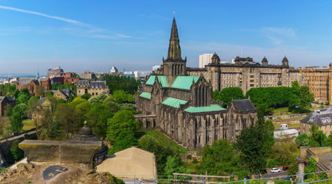 Glasgow Cathedral with steeple and lovely mature green patina on the roofs on a bright day