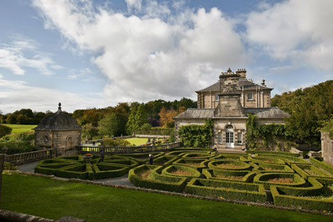 Pollok House - elegant grey sandstone building with maze garden in foreground