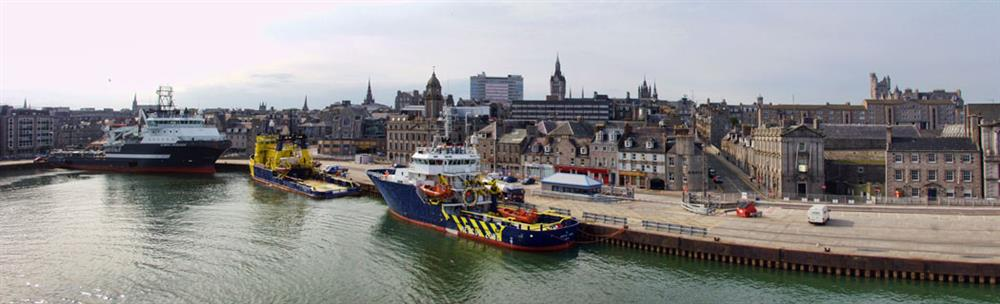 panoramic view of ships and vessels docked at Aberdeen Harbour with the city in the background