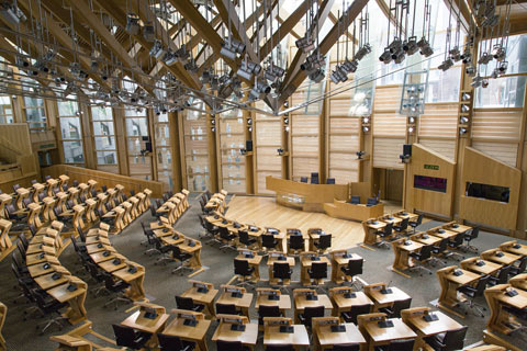 desks arranged in concentric semi-circles inside the Scottish Parliament