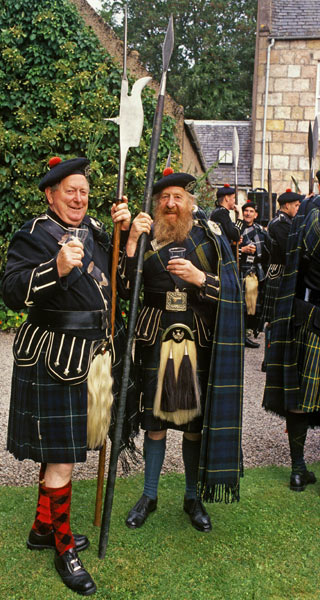 Men wearing sporrans, tartan kilts and cloaks holding large spears at a gathering