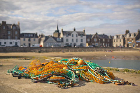 Bright green and yellow fishing net in foreground on a beach in an Aberdeenshire Fishing Village