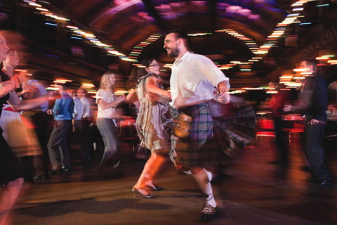 Slightly blurred image of man and woman spinning around in dance at a ceilidh