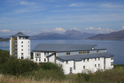 Modern white buildings comprising the Gaelic College on Skye with sea and mountains in background on a bright sunny day