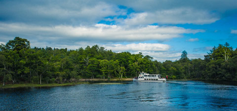 A white double-deck boat stops at a tree-lined bay while cruising Loch Lomond
