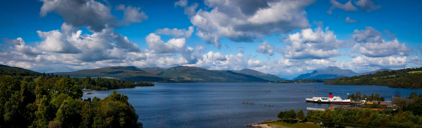 Panorama of Loch Lomond showing the Maid of the Loch paddle steamer and the mountains of the Arrochar Alps