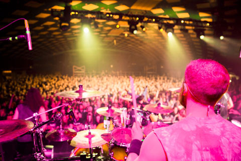 Drummer in forground playing to large crowd in background at Barrowlands