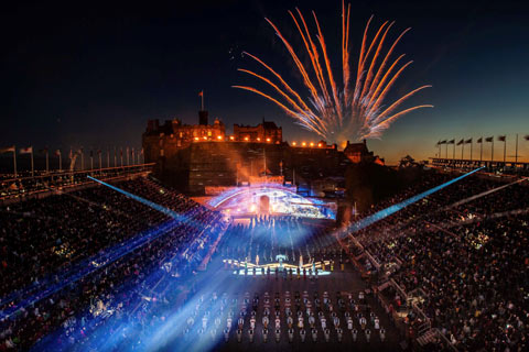 Fireworks next to floodlit Edinburgh Castle with audience, pipe bands and drummers at Edinburgh Tattoo