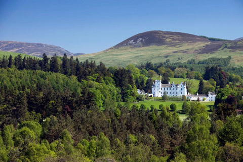 Blair Castle - striking white castle set amongst verdant woodland with hills in background