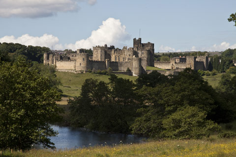 The turrets and defensive walls of Alnwick Castle seen across the River Aln