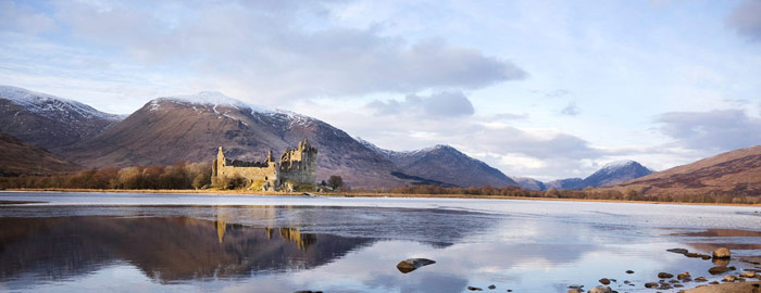 Kilchurn Castle - sand coloured ruined castle on banks of calm loch with snowy mountain peaks in background
