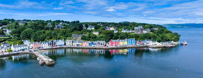 Tobermory - colourul houses along the bay and blue sky reflected in calm water
