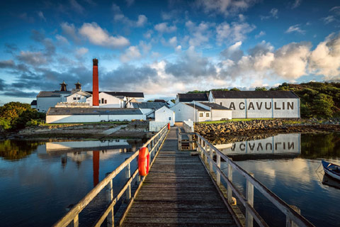 wooden bridge with railings leading over calm water  to low white buildings showing writing Lagavulin Distillery